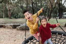 brother and sister on a large swing in the park for a photography session