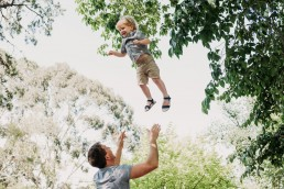boy being thrown up in the air by dad