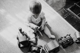 baby sitting plating with a toy wooden train