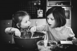 sisters mixing scones in a mixing bowl in the kitchen from clarke lifestyle family session