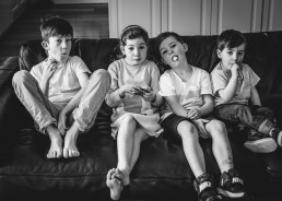 four sibling sitting on a couch eating lollypops during lifestyle photographs
