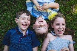 siblings laying in the grass laughing during an outdoor family lifestyle session