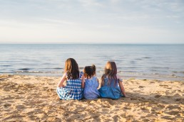 three sisters sitting on a beach looking at the water