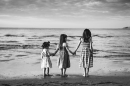 three sisters holding hands at the beach facing the water