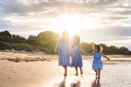 sisters walking along the beach holing hands at sunset