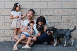 family of five plus their dog lifestyle family portrait sitting against a wall for fundraising day session