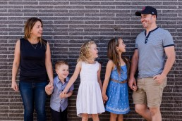 family of five leaning against a wall all laughing at dad