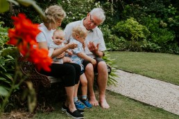 lifestyle portrait of grandparents with two grandchildren in the garden during their grandparents family session