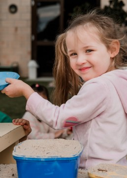 kindergarten girl playing with sand