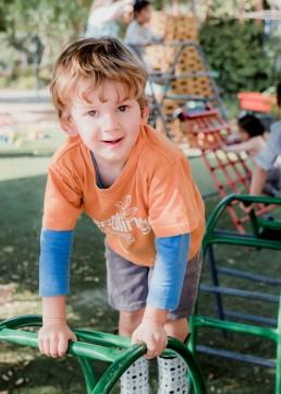kindergarten boy climbing on an aframe