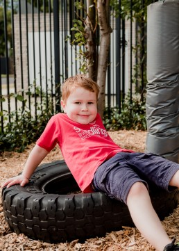 kindergarten boy sitting in a tyre