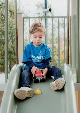 portrait of a kindergarten boy on a slide