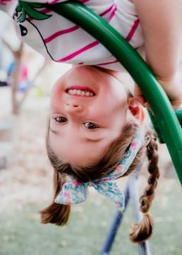 kindergarten girl upside down on an aframe