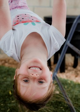 kindergarten girl upside down on a frame
