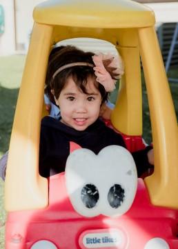 kindergarten girl playing in a ride in car