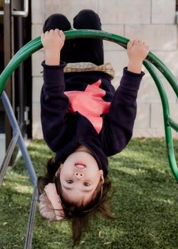 kindergarten girl upside down on a frame
