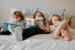 hree siblings on the family bed reading books