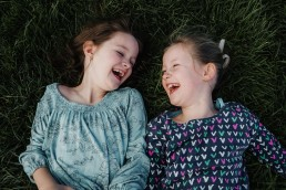 two girls laying on the grass laughing