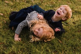 siblings rolling on the grass laughing