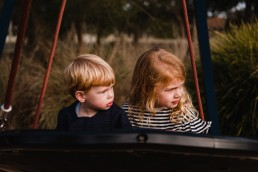siblings on a swing at the playground
