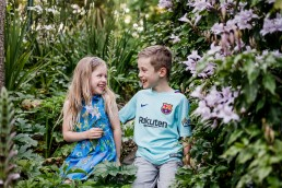 brother and sister siblings sitting in the garden laughing